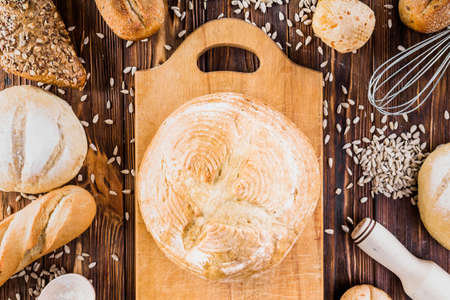 Different baking buns, croissants, gingerbread cookies. Delicious freshly baked bread on wooden background with place for text. Fresh loaves of bread And sliced breads containing sesame seeds. Stock Photo