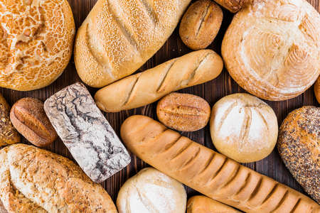 Different baking buns, croissants, gingerbread cookies. Delicious freshly baked bread on wooden background with place for text. Fresh loaves of bread And sliced breads containing sesame seeds. Imagens