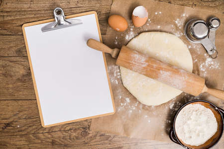 Flour and kitchen utensils whisk, baking dish, rolling pin with eggs on the table. Baking, cooking concept, top view with place for text.