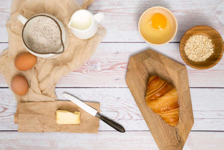 Flour and kitchen utensils whisk, baking dish, rolling pin with eggs on the table. Baking, cooking concept, top view with place for text. Zdjęcie Seryjne