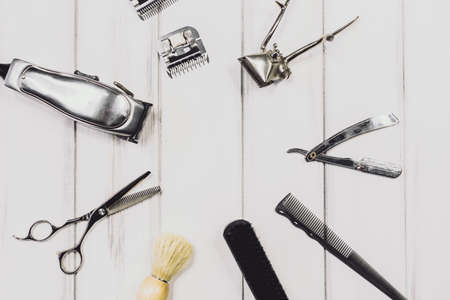 Vintage tools of barber shop on wooden background. Electric hair trimmer, vintage straight razors, a comb, wax and brush on the wooden background, close-up. Place to insert your text. Hipster grooming Imagens