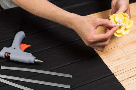 Woman glues glue gun. Woman doing craft jewelry. Women's handicrafts. The concept of creativity.