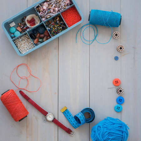 Box with beads, spool of thread, plier and glass to create hand made jewelry on wooden background with place for text. Top view