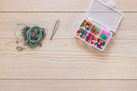 Making of handmade jewelery. Box with beads on old wooden table. Top view with woman hands. Beads and skeins of thread.