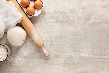 Flour and kitchen utensils whisk, baking dish, rolling pin with eggs on the table. Baking, cooking concept, top view with place for text. 版權商用圖片