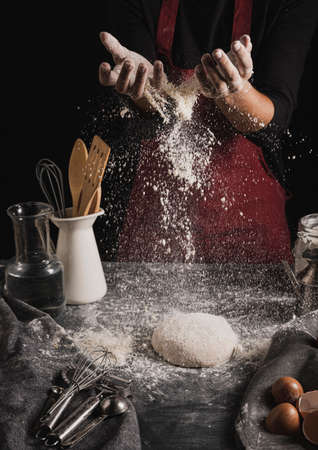 Beat flour and kitchen utensils, a baking dish, a rolling pin with eggs on the table. Baking, cooking concept. Chef making bread and gingerbread cookies. The cook kneads and rolls the dough. 版權商用圖片