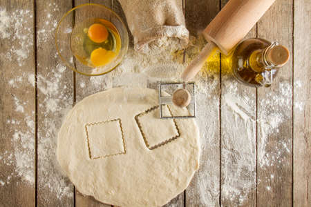 Flour and kitchen utensils whisk, baking dish, rolling pin with eggs on the table. Baking, cooking concept, top view with place for text. 免版税图像