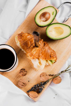 Delicious Breakfast with Croissant sandwiches with Fried Egg, Salad Leaves and avocado. Coffee, healthy breakfast. 免版税图像