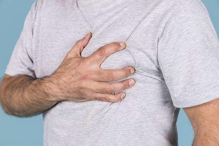 close up man s hand holding his heart pain. Resolution and high quality beautiful photo