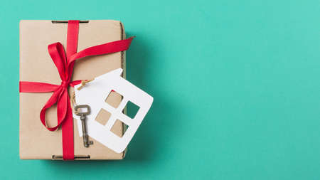 brown gift box tied with red ribbon house key turquoise surface. Resolution and high quality beautiful photo