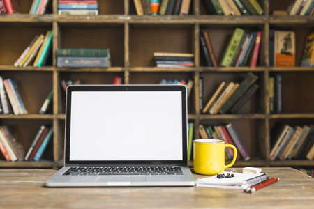 coffee mug laptop with stationeries wooden desk library. Resolution and high quality beautiful photo