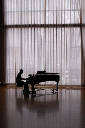 grand piano: silhouette pianist in a sunlit studio