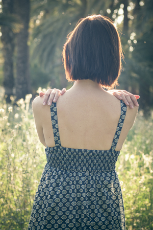 Back portrait of a woman in the sunlight, hugging herself under the golden light of the Summer
