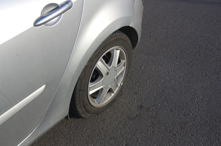 puncture: View from above flat tire. Puncture on the road in a modern car.Close-up punctured wheel.