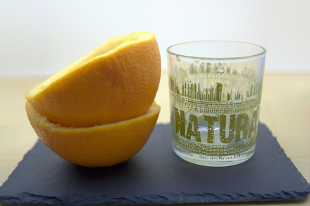 healt: An empty glass of freshly squeezed orange juice with the word Natural written on it. Next to an orange already squeezed.