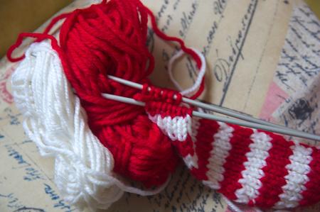 Madejas de lana y agujas para tejer una bufanda textil roja y blanca con fondo dorado Foto de archivo