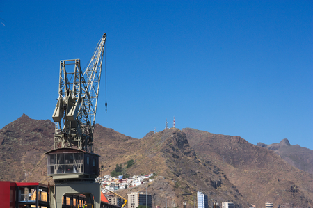 Harbor crane with a mountain in the background.