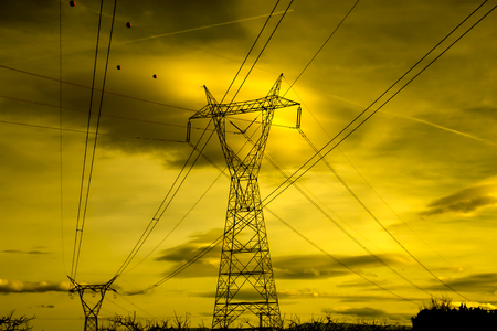 Electrical transmission tower landscape. Electrical power lines silhouetted against sky at sunset. Energy concept. Stock Photo