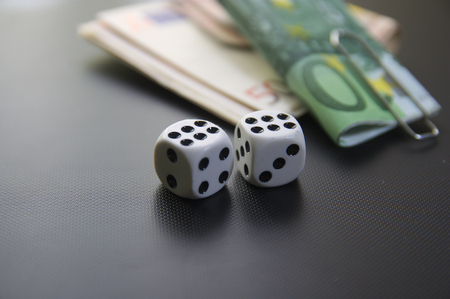 Two dice with bundles of money with black background. Wads of tickets won  wagered in the game. Side view. Stock Photo