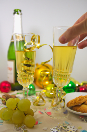 Someone takes a drink from a table where there are bottles of sparkling wine, Christmas sweets and lucky grapes, along with typical Christmas and New Year decorations. Standard-Bild