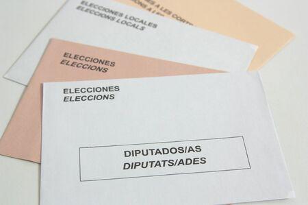 Vista de sobres electorales españoles de colores blanco y sepia en abanico sobre una mesa. Las palabras que se ven están en español (Elecciones, elecciones locales, diputados) y en inglés significan (elecciones, elecciones locales, diputados)