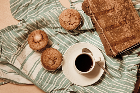 Flat lay of a snack with muffins, a cup of coffee and an old book on a green improvised doily