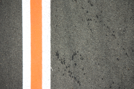Three vertical white and orange lines on gray asphalt with space for texts on the right (copy space) Imagens