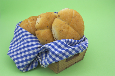 A few sweet breads inside a wooden crate and a rag of white and blue squares on a green background Stock Photo