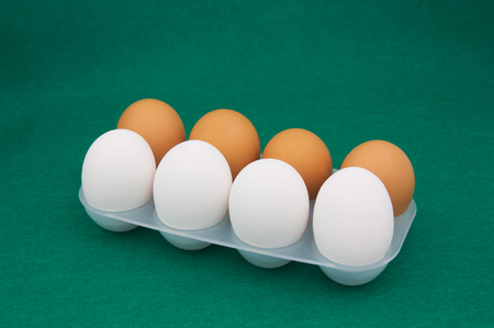 Tray with 8 eggs, half white and the other half brown on a green mat