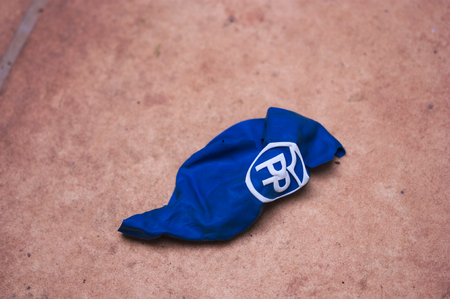 April, 2019. Spain. A blue balloon with the initials of the political party Popular Party of Spain broken and forgotten metaphor of what happened in the last elections is seen on the ground