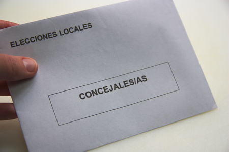 Someone holds an envelope in which he deposits the vote for local elections in Spain. Appears written in Spanish: Local Elections and Councilors