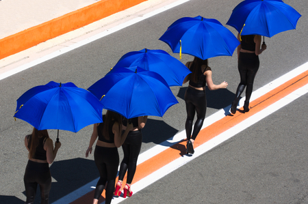 Women with umbrellas to shelter from the sun walk following lines drawn on the asphalt