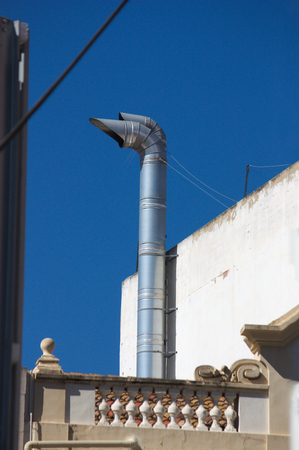 Metal chimney duct that pulls fumes from the kitchen of lower houses Standard-Bild - 122302282