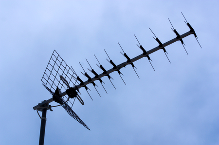 Silhouette of a domestic television antenna on a roof of a building in the city Stock Photo