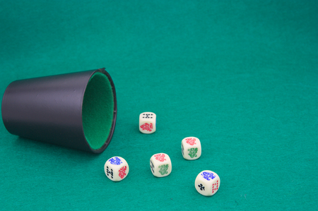 Close-up of a beaker with poker dice on a green game table