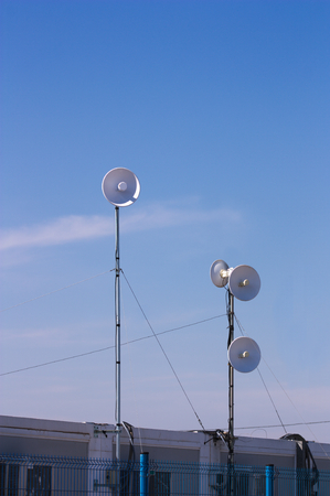 Several tall antennas directed in different directions to have better coverage. In the image the blue sky facilitates the addition of texts