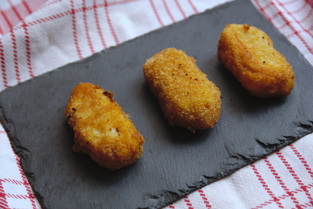 Three homemade croquettes served on a slate plate on a red striped mat on white