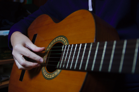 A close-up of a woman rehearsing with the Spanish guitar