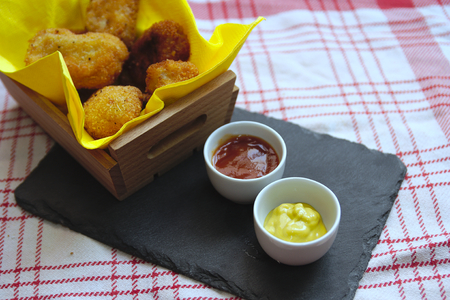 Serving tapas with homemade croquettes and tomato sauce and mustard
