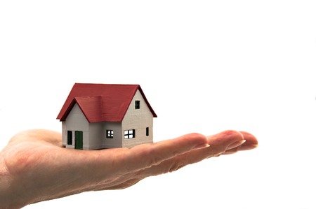 An image of a hand with a red roof house with blank background. Isolated