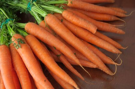 A pile of carrots on a wooden table occupying all the space of the image