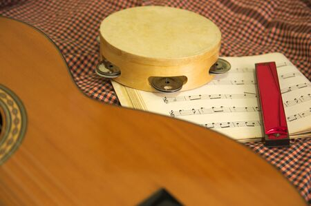 Instruments for traditional music, a Spanish guitar, a harmonica and a tambourine on scores of folk music Stock Photo