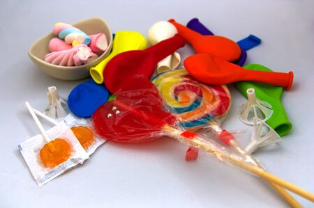 A white table full of candies, balloons, lollipops and jellybeans in many funny colors