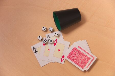 The four aces of the poker cards next to six dice of points and the rest of the deck without dividing Archivio Fotografico