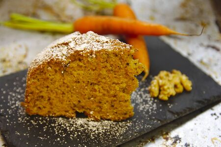 Carrot cake with sugar on top and some carrots and nuts on the side adorning the scene Stock Photo