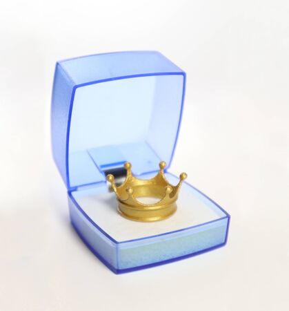 Gold Crown in a blue translucent gift box on white background