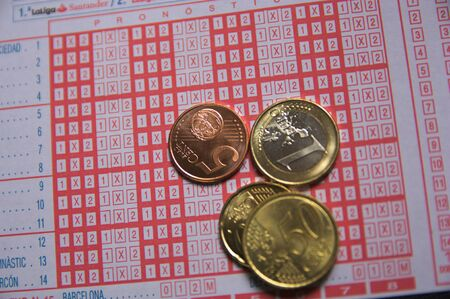 2018-Spain. Some euro coins on a Spanish lottery lottery ballot based on the results of the Spanish mens soccer league 스톡 콘텐츠