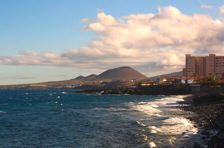View from the Caletillas beach of the volcano of the Special Natural Reserve of Malpais de G?imar and the holiday buildings of the coast of the island of Tenerife, in Spain Reklamní fotografie