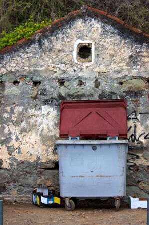 A dumpster next to an old house facade with a small window that looks like ruins Stock fotó