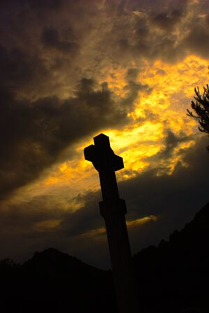 Silhouette of a Christian cross on a stunning red sky with clouds